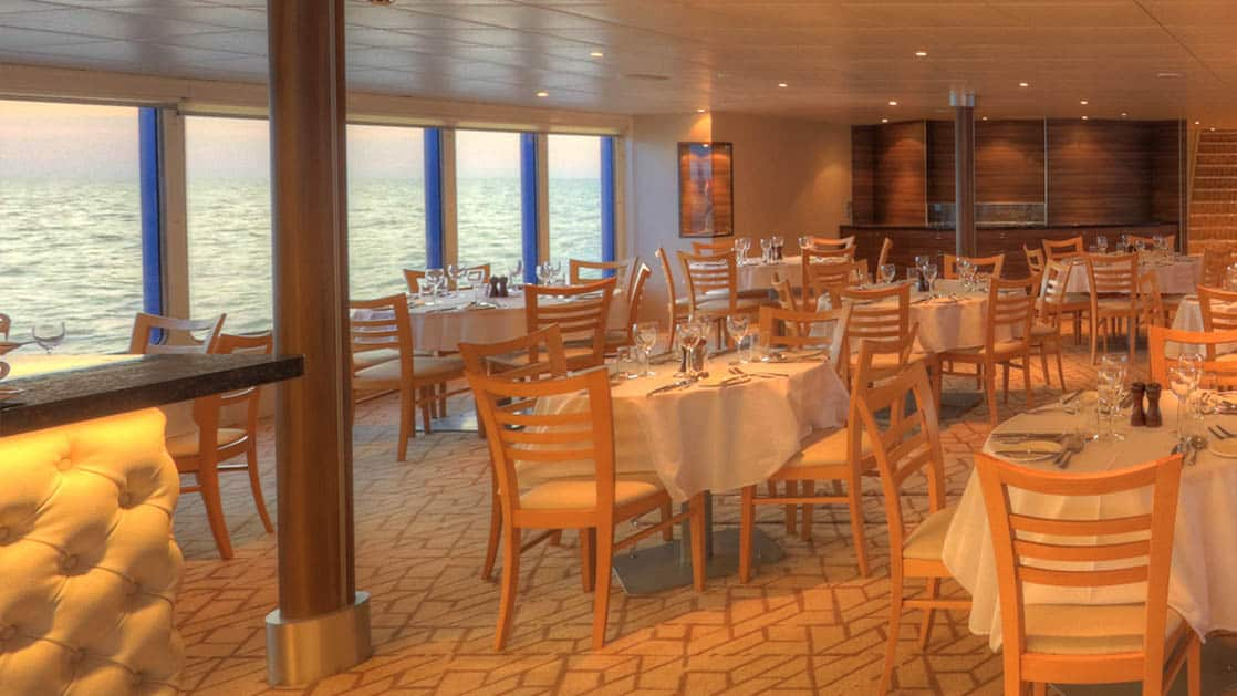Dining room with tables and windows aboard Coral Adventurer.