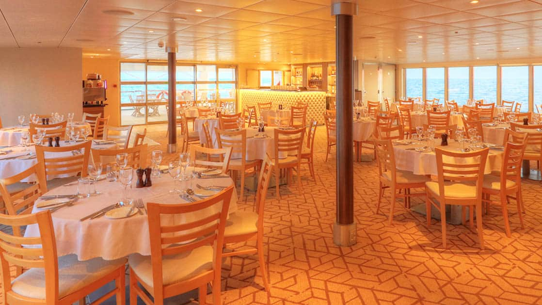 Empty dining room with many tables aboard Coral Adventurer.