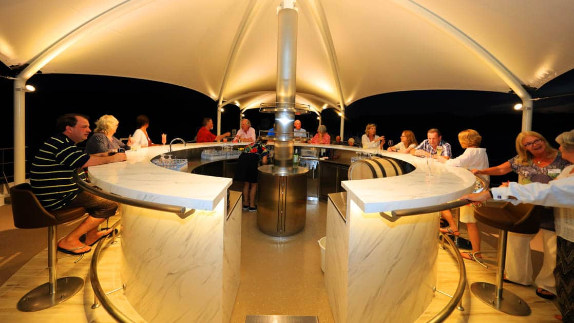 Sun deck bar with guests around the bar during the evening aboard Coral Adventurer.