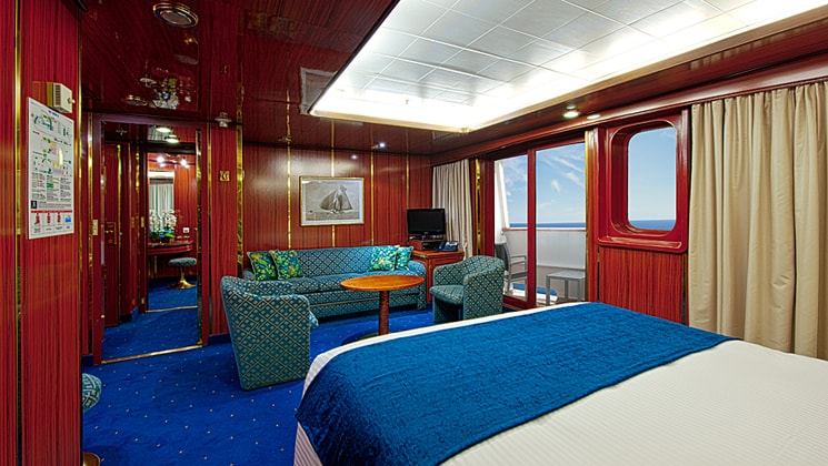 Suite 604 on the Corinthian small ship with a bed and large windows and a couch.