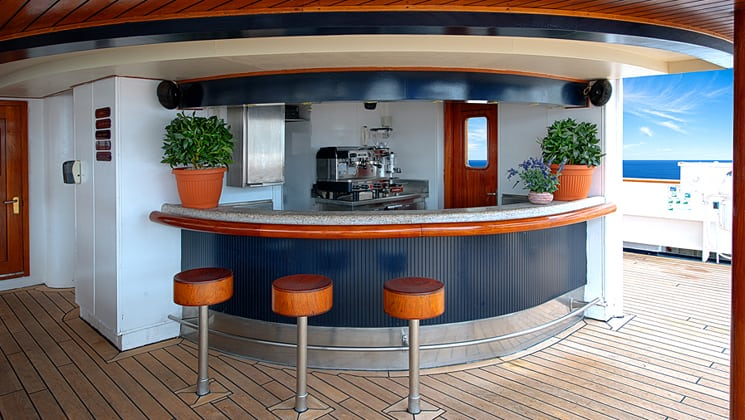 Corinthian small ship outdoor bar with stools and red door and open passageway to the deck.