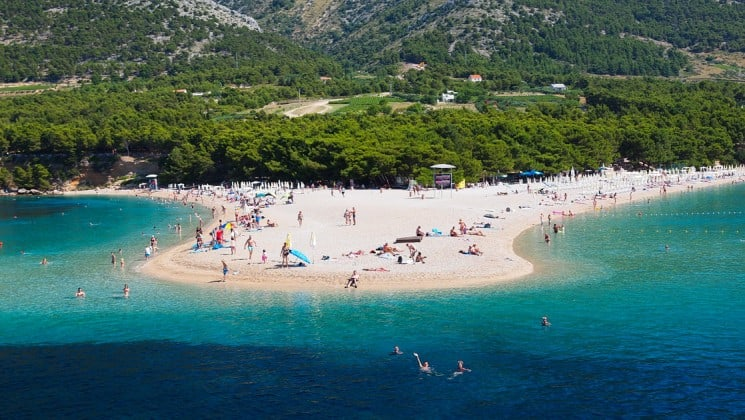 looking down at a beautiful croatia beach filled with adventure travelers in the middle of the day