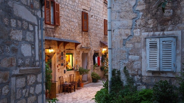a street in the town of hvar in the mediterranean with 2 chairs and a table outside an illuminated window