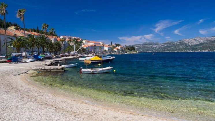 a sunny day at korcula beach croatia with small ships anchored in the mediterranean while travelers visit the town
