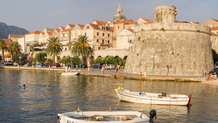 korcula croatia on a sunny day with small ships anchored in front of the town while travelers swim in the mediterranean