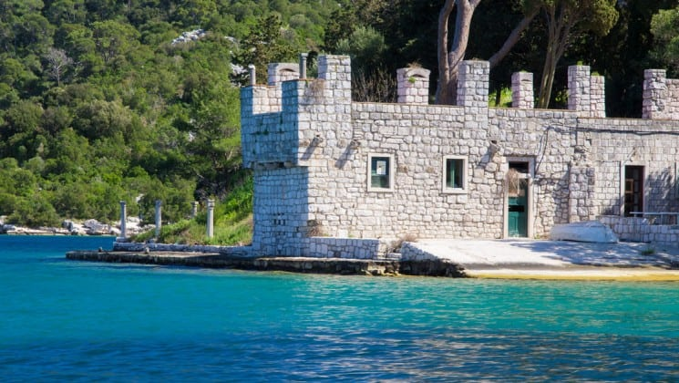 mljet islet croatia on a sunny day with a stone structure on the shore overlooking turquoise water
