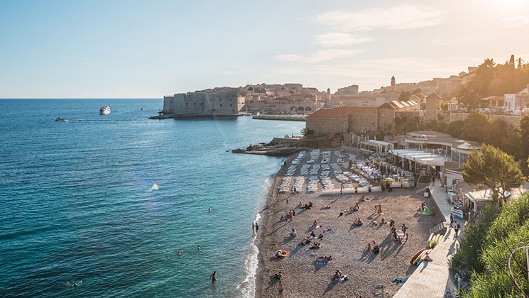 Aerial view of seaside Mediterranean city at sunset, with people on the beach & stone buildings in the background.