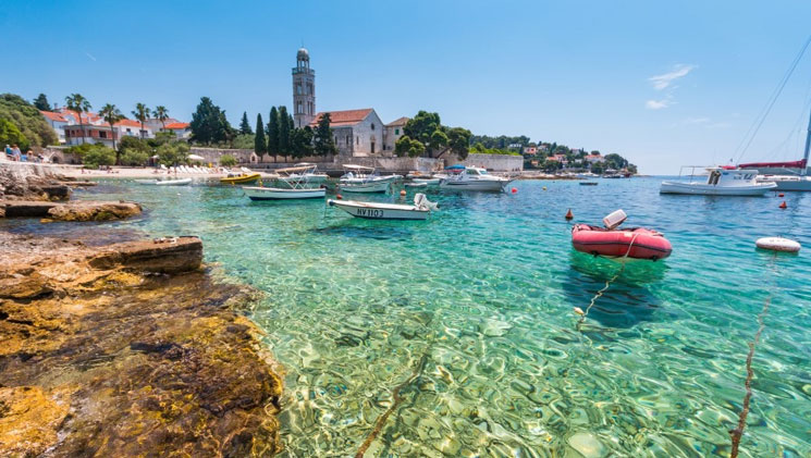 Clear turquoise water in a harbor with various small day boats on moorings beside a medieval Mediterranean city on a sunny day.