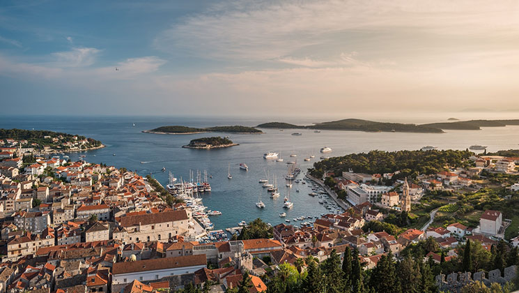 aerial view of seaside mediterranean city at sunset, with stone buildings, terracotta roofs & ships in the harbor.