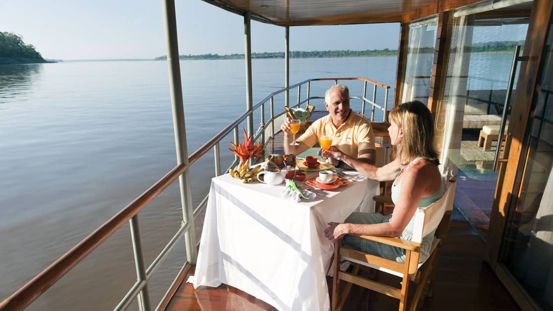 Couple dining on the private balcony of a Deluxe Suite aboard Delfin I on the Amazon River