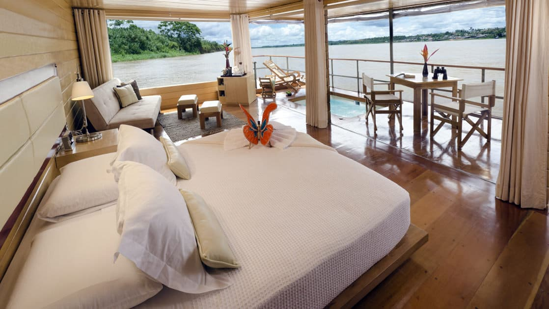 Inside a Deluxe Suite with bed, couch and private balcony with table, chairs, Jacuzzi and lounge chair aboard Delfin I on the Amazon River