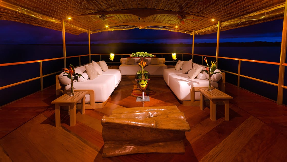 Lounge area with three couches on the Top Deck at night aboard Delfin I on the Amazon River