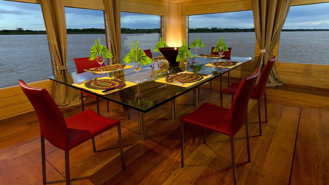 Glass dining table with seating for six near large picture windows in dining room aboard Delfin I on the Amazon River