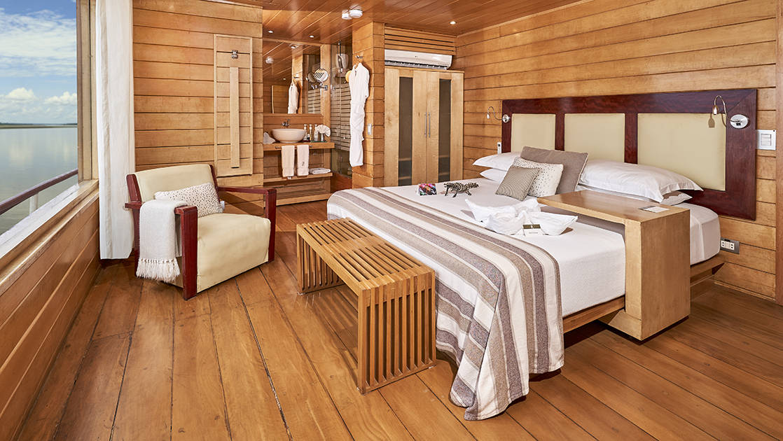 Suite aboard Peru Amazon riverboat Delfin II, showing double bed, chair, ensuite bathroom & wood & white accents throughout.