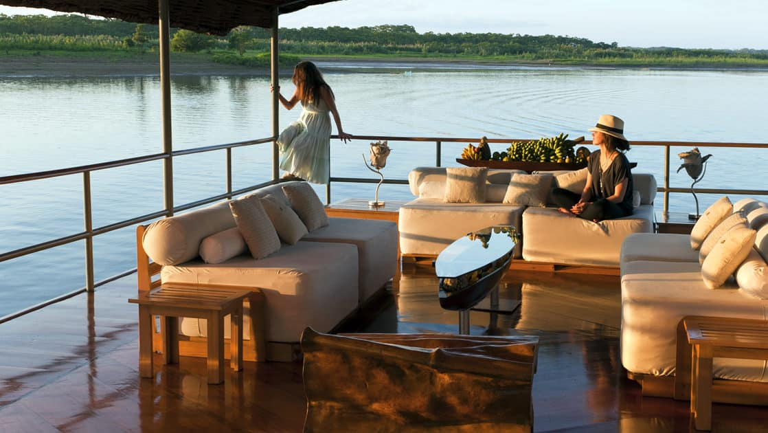 Three couches at the outdoor lounge area on the top deck aboard Delfin I on the Amazon River