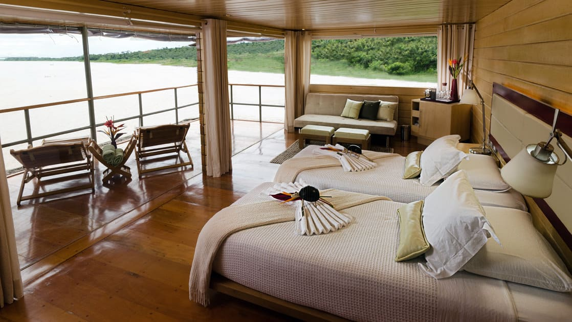 Master Suite with two beds, couch and private balcony with lounge chairs aboard Delfin I on the Amazon River