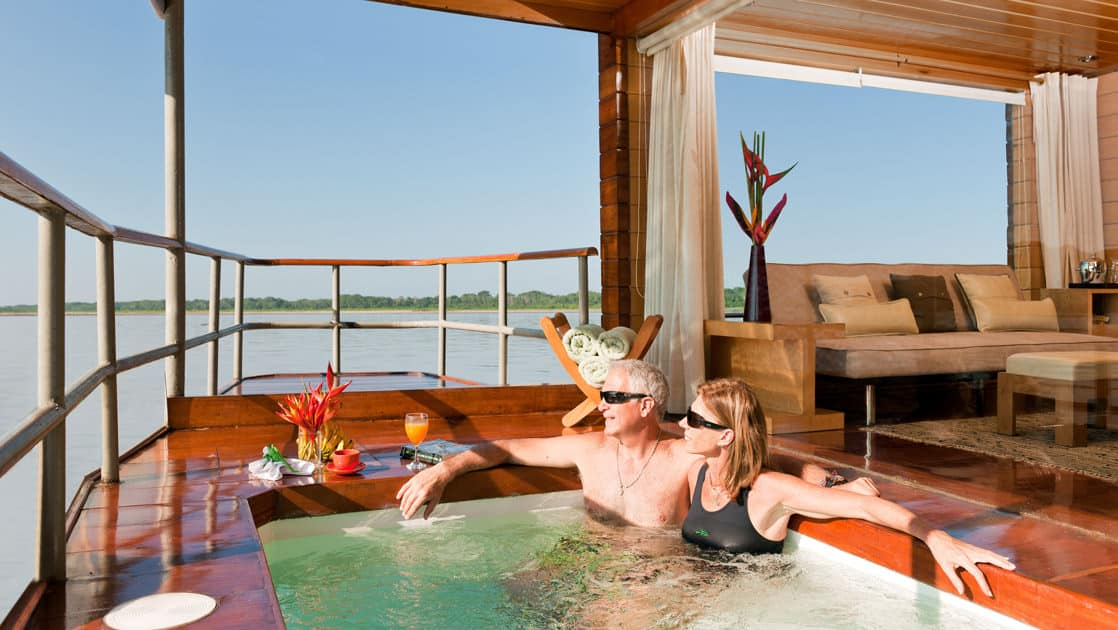 Couple in a private whirlpool outside a Deluxe Suite aboard Delfin I on the Amazon River