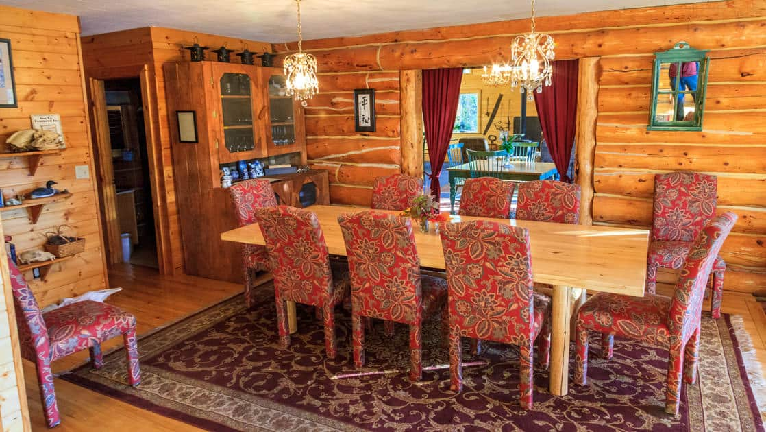 The dining room with a long table and eight chairs inside the wood cabin at Winterlake Lodge, an Alaska wilderness resort