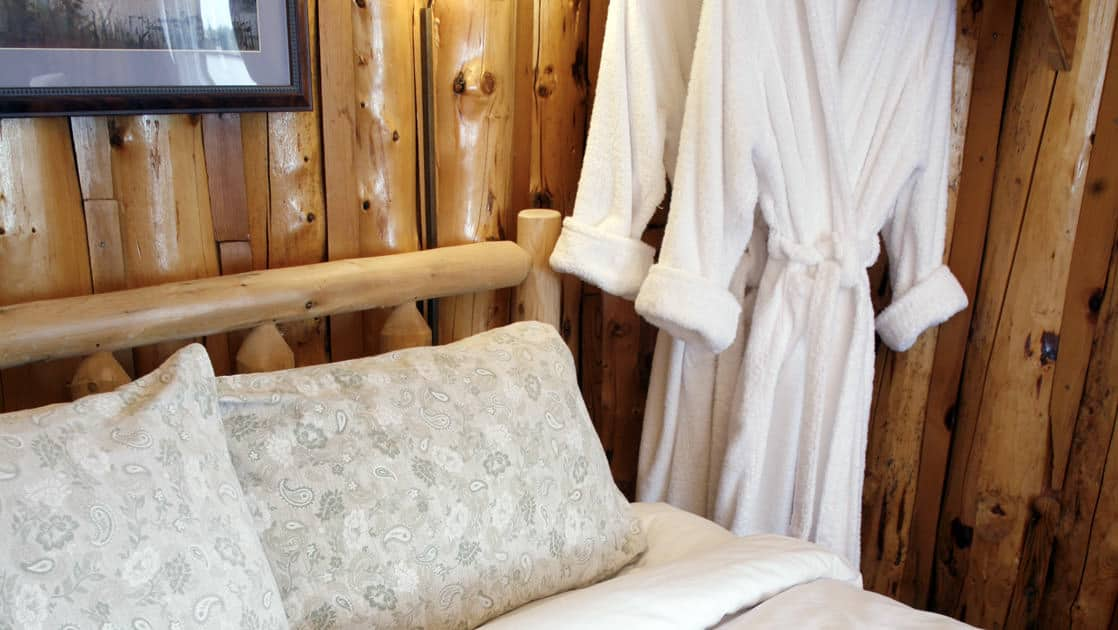 Two robes hang next to a double bed inside a cabin at Winterlake Lodge, an Alaska resort recognized by National Geographic for its wilderness experience