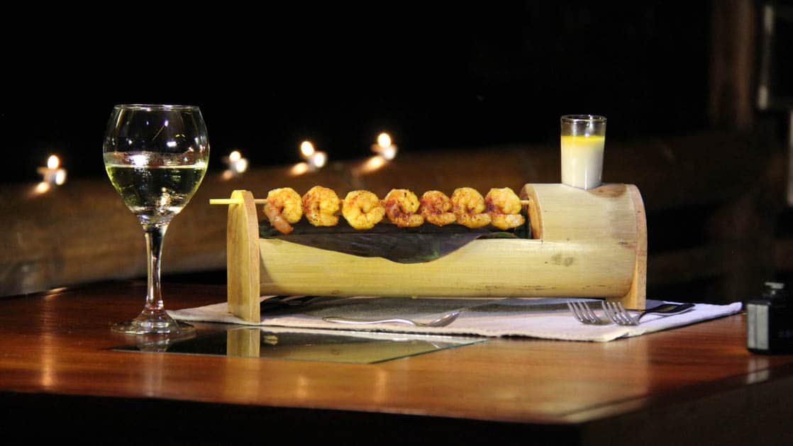 Skewered shrimp and a glass of wine are served on a table at La Selva Ecolodge, a sustainable, luxury accommodation in Ecuador
