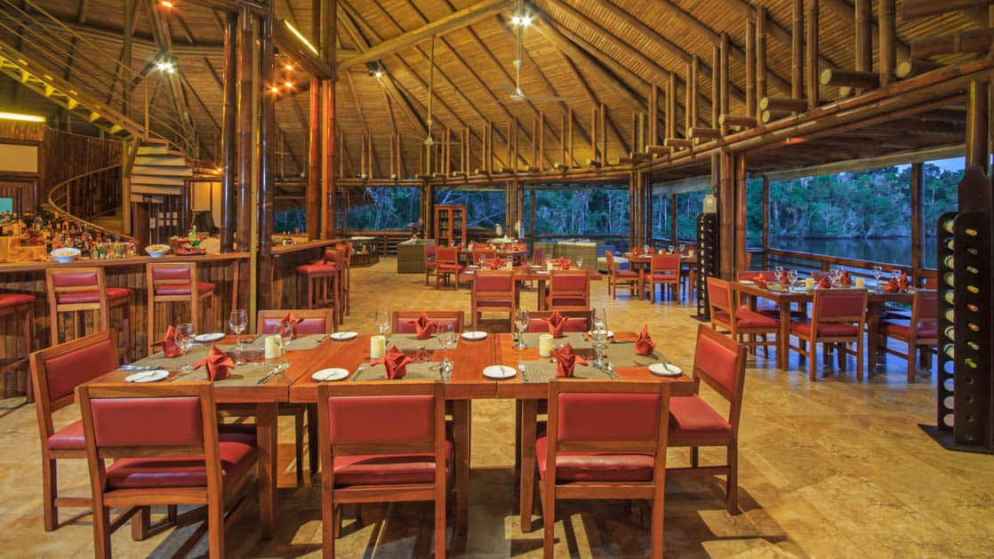 Inside the open-air dining room, with a thatch-roof and wood tables set for a gourmet meal with local ingredients at La Selva Amazon Eco Lodge, a sustainable, luxury accommodation in Ecuador overlooking Lake Garzacocha