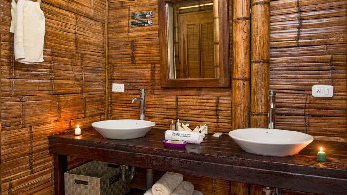 Two sinks and a mirror are part of the vanity in the bathroom of the family suite at La Selva Amazon EcoLodge, a sustainable, luxury accommodation in Ecuador. Guests have hot showers.