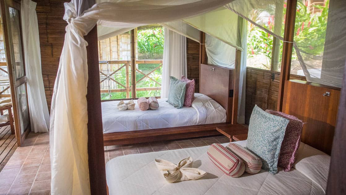 The family suite at La Selva Amazon EcoLodge, a sustainable, luxury accommodation in Ecuador, with double beds, an open-air setting, mosquito nets, and jungle views
