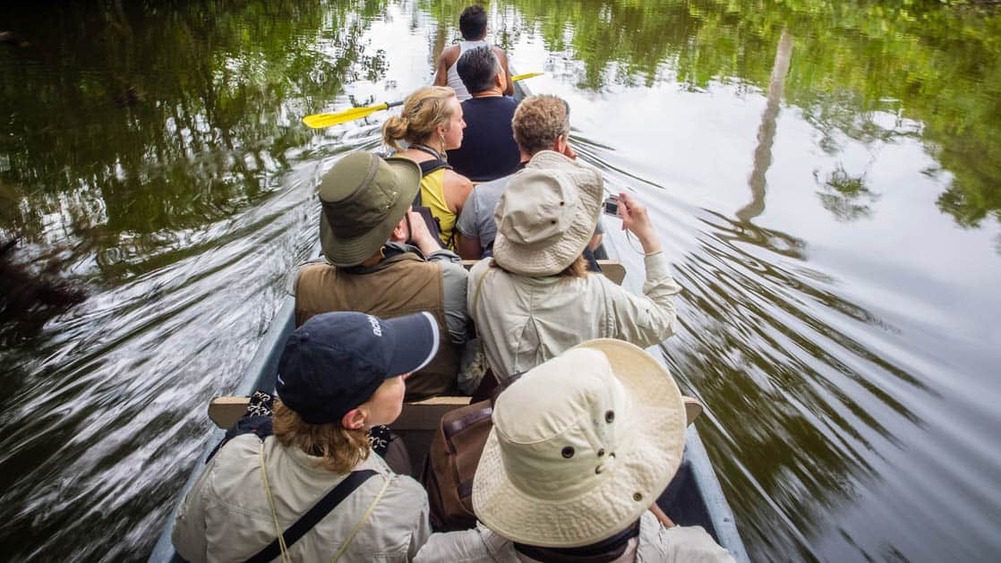 A group of jungle travelers and bird-watchers paddle down the river in a canoe while staying at La Selva Ecolodge, a sustainable, luxury accommodation in Ecuador