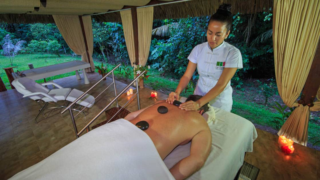 A guest relaxes at a massage table and receives a spa treatment at La Selva Ecolodge, a sustainable, luxury accommodation in Ecuador