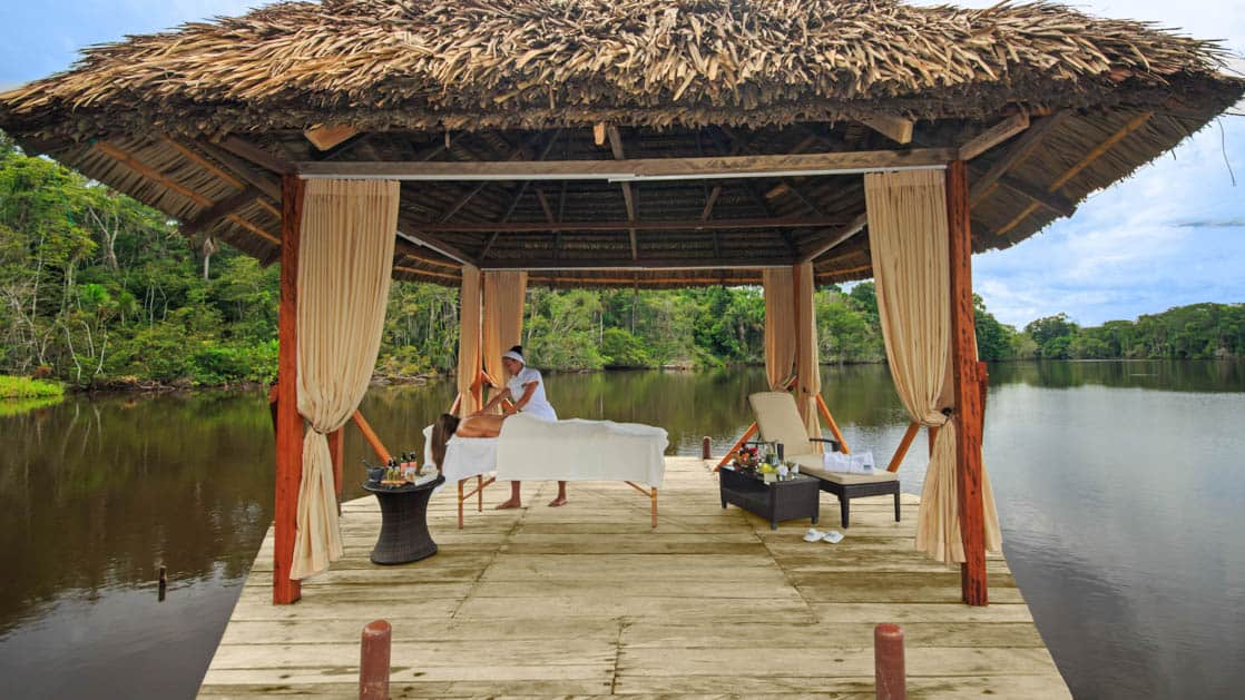 A guest receives a massage and spa treatment on a covered patio on the lake at La Selva Ecolodge, a sustainable, luxury accommodation in Ecuador