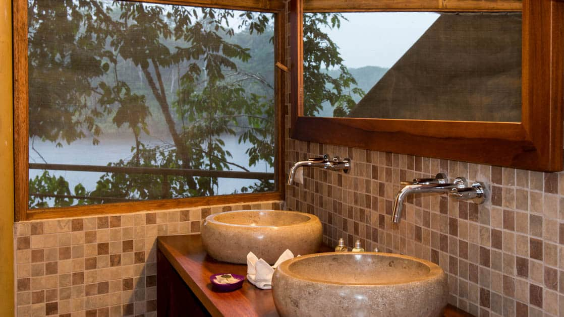 Enjoy hot water and showers with a view of the jungle from the bathroom of the scenic suite at La Selva Amazon EcoLodge, a sustainable, luxury accommodation in Ecuador.