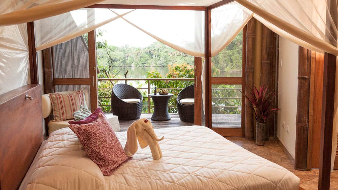 A king-sized bed, fresh linens, and a private balcony overlooking the jungle are all a part of the scenic suite at La Selva Amazon EcoLodge, a sustainable, luxury accommodation in Ecuador.