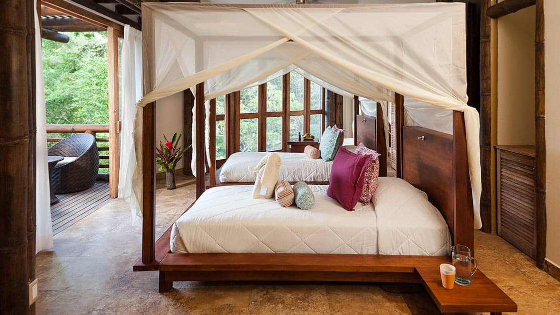 The Superior Suite at La Selva Amazon EcoLodge, a sustainable, luxury accommodation in the Ecuadorian Amazon basin, with a double beds, mosquito nets, and a private balcony with a rainforest view