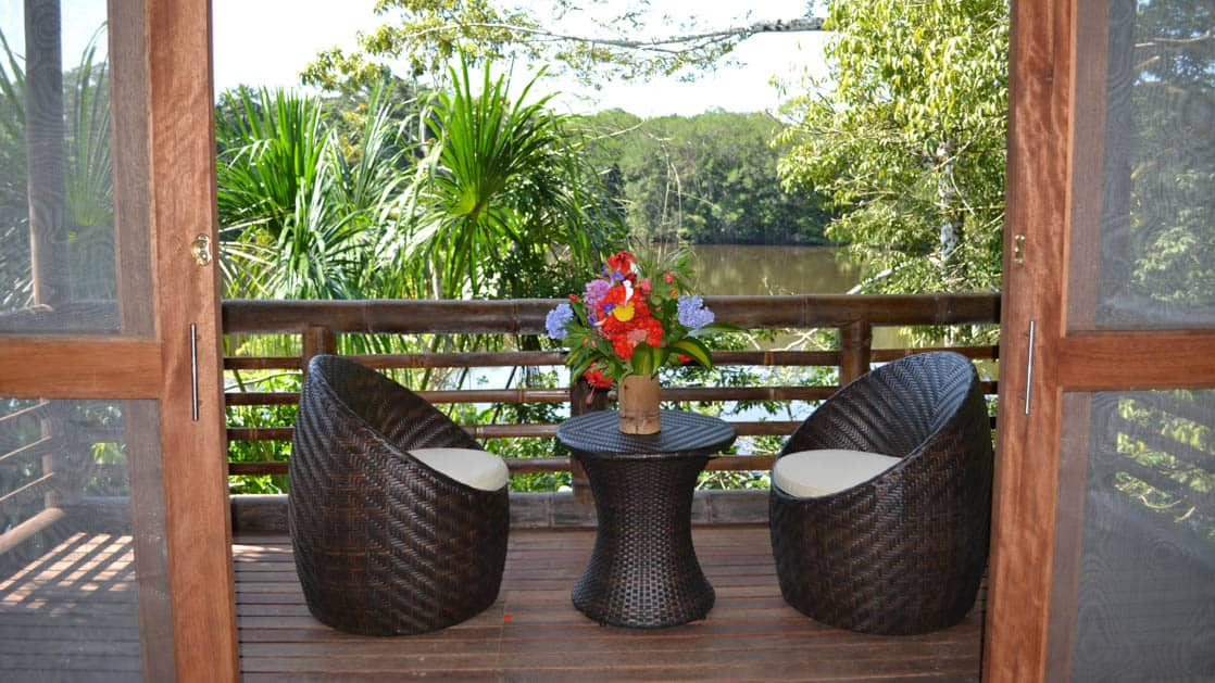 The private balcony of a superior suite overlooks Lake Garzacocha with panoramic jungle views, seating, table, fresh flowers at La Selva Amazon EcoLodge in Ecuador