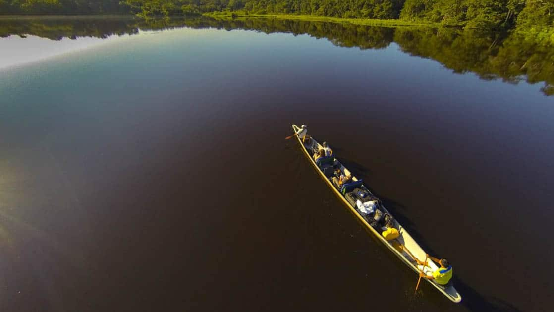 A canoe cuts through still water in the lake near the Napo Wildlife Center, a sustainable eco lodge surrounded by a 53,000 acre rainforest biosphere reserve within Yasuni National Park in the Amazon.
