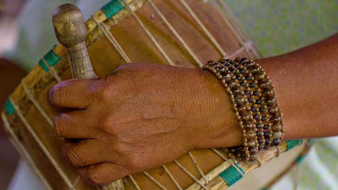 An arm holds a traditional Ecuadorian drum, with a bracelet on the wrist, at the Napo Wildlife Center, a sustainable eco lodge surrounded by a 53,000 acre rainforest biosphere reserve within Yasuni National Park in the Amazon.
