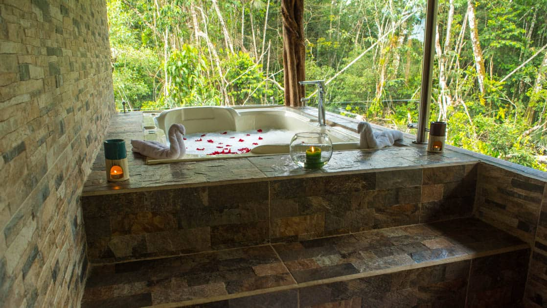 A jacuzzi set in stone tile with red flower petals, candles, and towels at the Panoramic Suite at the Napo Wildlife Center, a luxury eco lodge surrounded by a rainforest biosphere reserve in the Ecuadorian Amazon.
