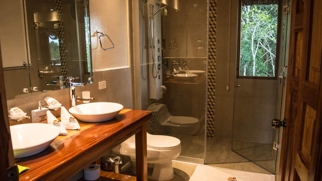 Two sinks and a vanity, with a toilet and a hot shower, inside the bathroom of the Panoramic Suite at the Napo Wildlife Center, a luxury eco lodge surrounded by a rainforest biosphere reserve in the Ecuadorian Amazon.