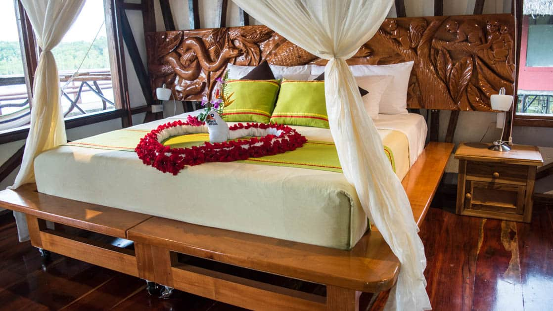 Fresh flowers are arranged on a king-sized bed with fresh drapes inside the Panoramic Suite at the Napo Wildlife Center, a luxury eco lodge surrounded by a rainforest biosphere reserve in the Ecuadorian Amazon.