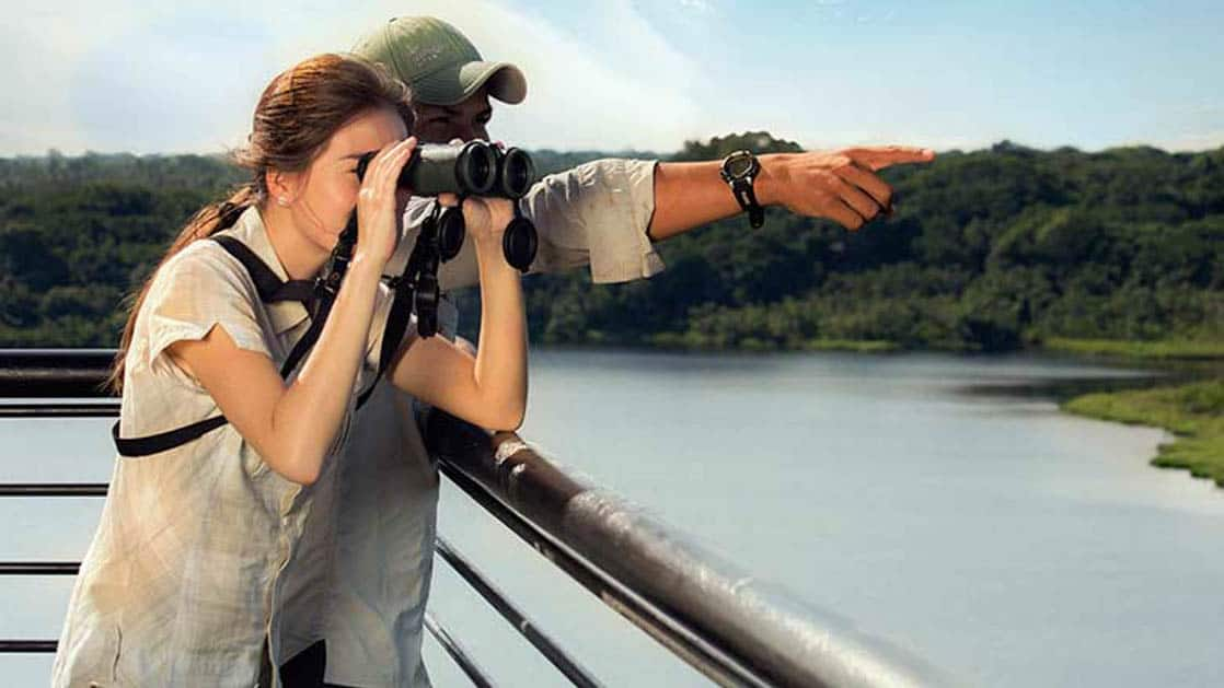 A traveler looks through binoculars while another traveler points, near the Napo Wildlife Center, a sustainable eco lodge surrounded by a 53,000 acre rainforest biosphere reserve within Yasuni National Park in the Amazon.