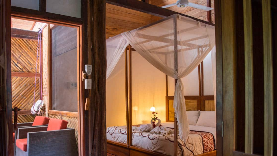 A corner view of the center suite at the Napo Wildlife luxury eco-hotel in the Ecuadorian Amazon, with a glimpse of the deck and the queen-sized bed.