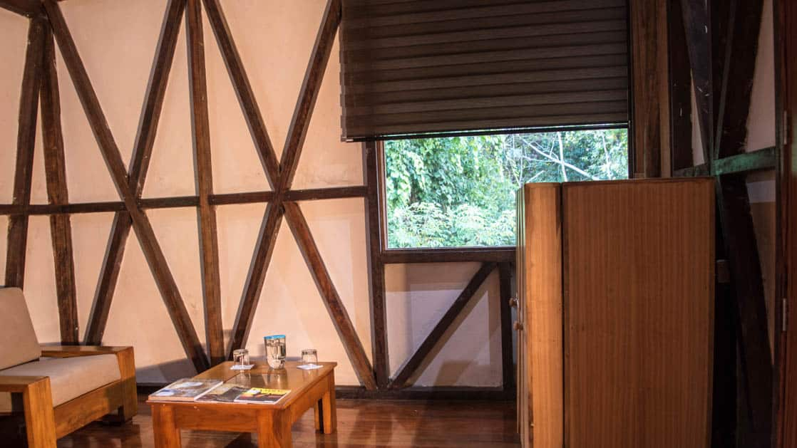 The living room with traditional woodwork, a chair and table, in a suite at the Napo Wildlife Center, a luxury eco lodge surrounded by a rainforest biosphere reserve in the Ecuadorian Amazon.