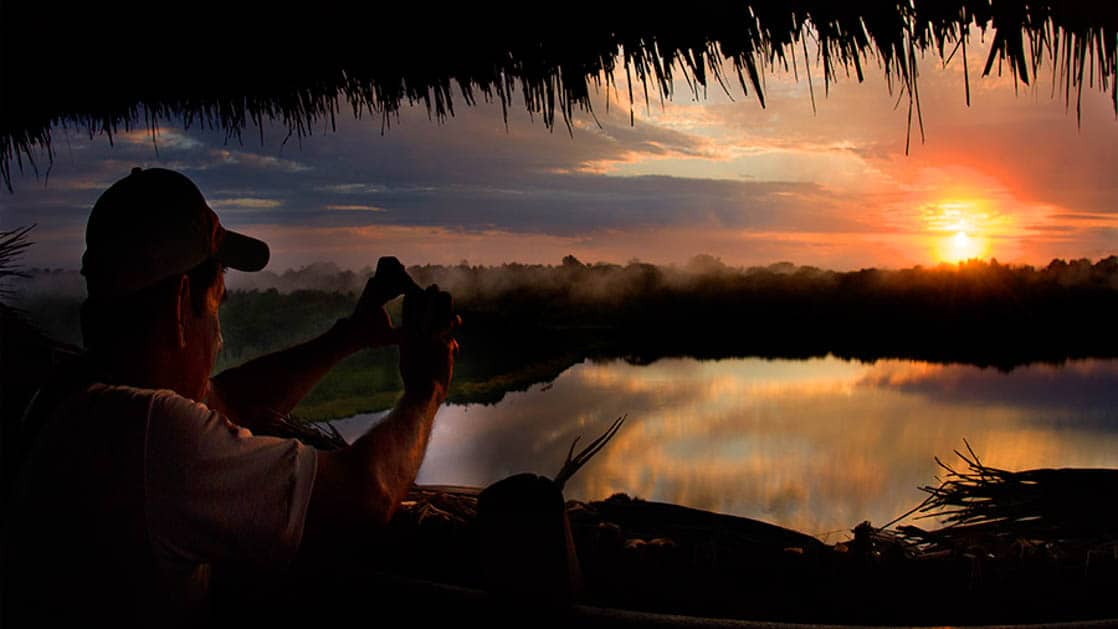 A guest watches the sunset over the rainforest and the water from the Napo Wildlife Center, a luxury eco lodge in Ecuador's Amazon