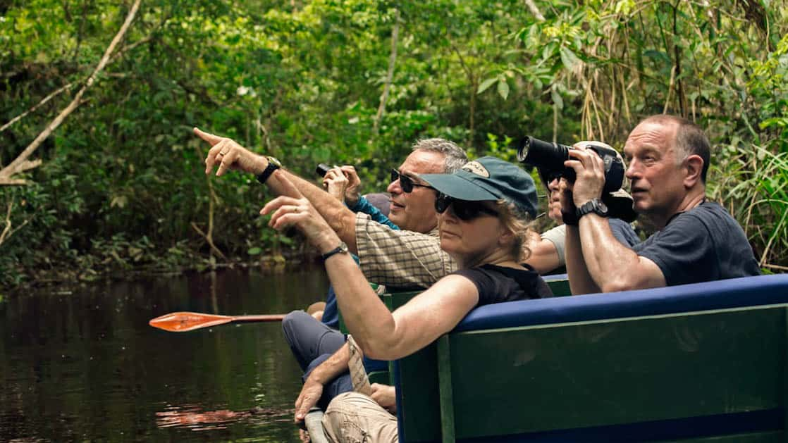 A group of travelers point at wildlife while sitting in a boat near the Napo Wildlife Center, a sustainable eco lodge surrounded by a 53,000 acre rainforest biosphere reserve within Yasuni National Park in the Amazon.