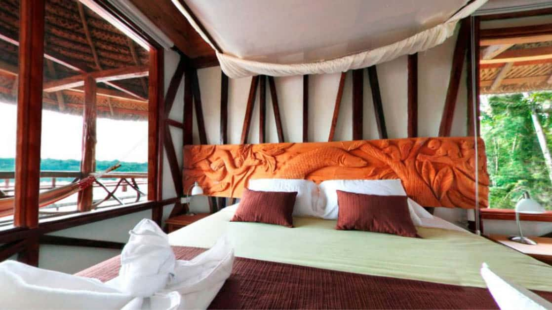 A king-sized bed with fresh maroon and white linens is made in a room displaying traditional Ecuadorian architecture and woodwork at the Napo Wildlife Center, a luxury eco lodge surrounded by a rainforest biosphere reserve the Amazon.