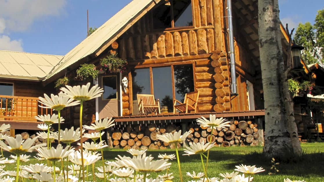Flowers bloom in front of the wood cabin exterior that is the Winterlake Lodge, recognized by National Geographic for its wilderness experience