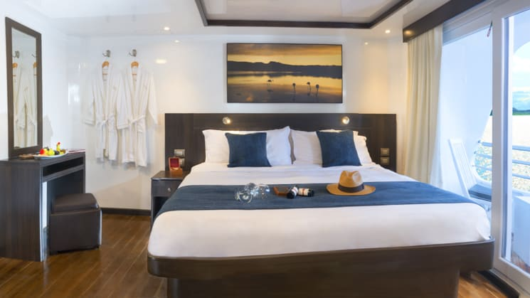 Suite with large bed, bedside table, vanity and private balcony aboard Cormorant catamaran in the Galapagos Islands