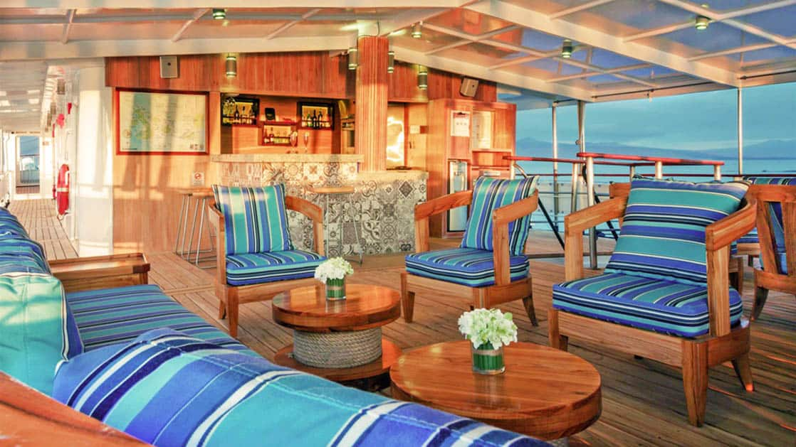 Outdoor couch and chairs and bar on the deck of the Evolution.