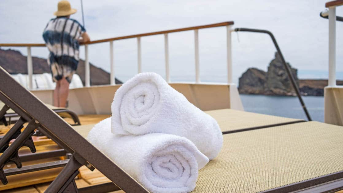 Lounge chairs with rolled towels with a Galapagos traveler looking out from the deck on the Evolution.