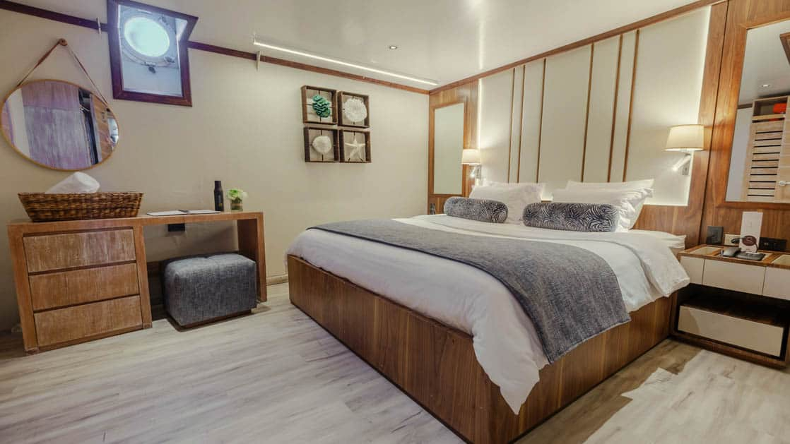 Evolution stateroom with double bed, dresser with desk, nightstand and porthole.
